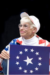 Photo of Barbara Coe holding flag