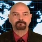 photo of Bob Powell in a suit in front of a world map