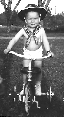 Photo of Doc C at 22 months riding a bicycle with a cowboy hat and bandana