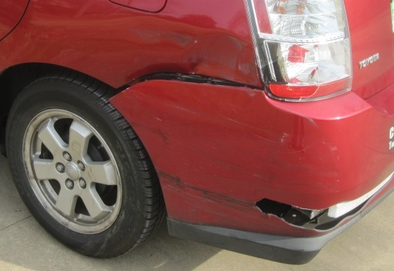 Photo showing collision damage to left rear of auto